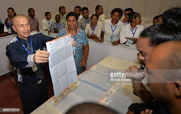 An election supervisor holds up votes for scrutineers to overlook at a local sports arena after the poll booths closed in the Fiji elections in the...