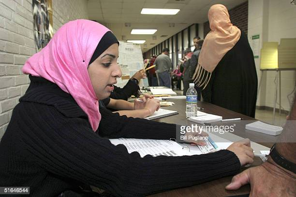An election volunteer checks in a voter at Salina School November 2, 2004 in Dearborn, Michigan. Polls are showing a tight race between the incumbent...