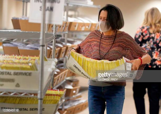 An election worker carries mail-in ballots in US Postal Service containers to be processed by election workers at the Salt Lake County election...