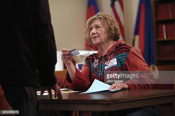 An election worker checks a voter's identification against a registration list at a polling center on April 26 2016 in Stamford Connecticut...