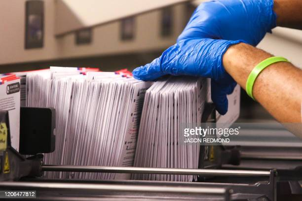 An election worker handles vote-by-mail ballots coming out of a sorting machine for the presidential primary at King County Elections in Renton,...