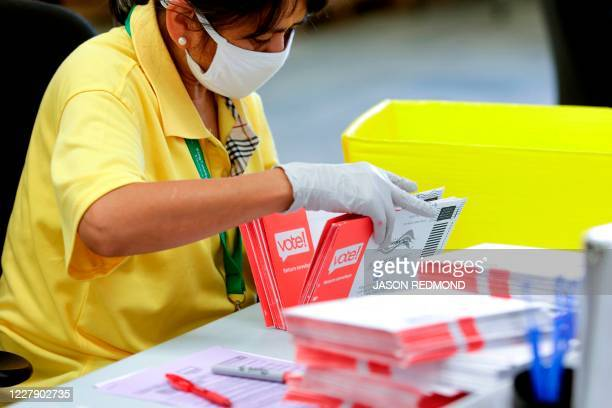 An election worker opens envelopes containing vote-by-mail ballots for the August 4 Washington state primary at King County Elections in Renton,...