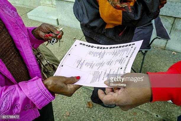 An election worker passes out sample ballots to voters as they arrive at a polling location in Aliquippa Pennsylvania US on Tuesday Nov 8 2016 The...
