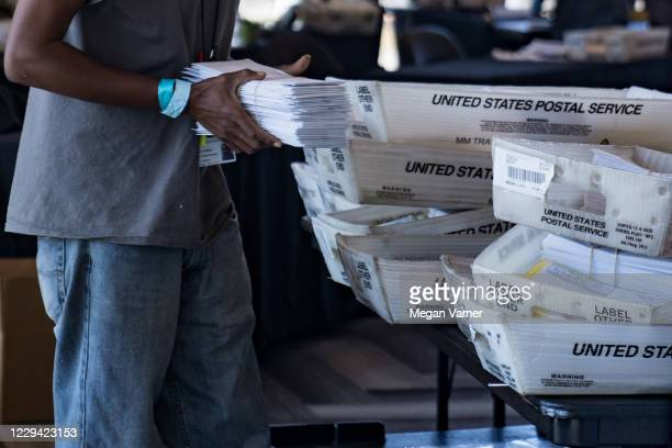 An election worker processes absentee ballots at State Farm Arena on November 2 2020 in Atlanta Georgia With recordbreaking early voting turnout...