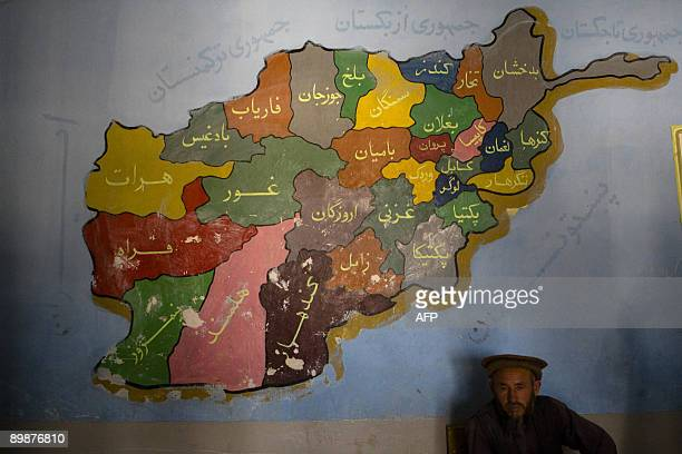 An election worker sits under a map of Afghanistan in MazarESharif on August 19 2009 Millions of Afghans vote for a president on August 20 for only...