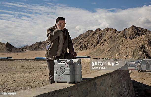 An election worker talks on the phone as he stands with voting machines while leaving a central collection point to head for a polling station on May...