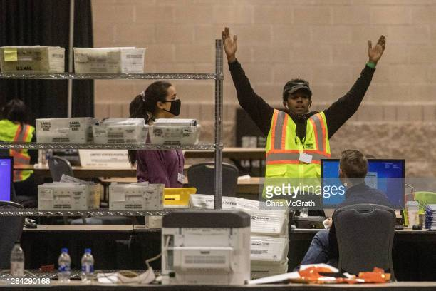 An election worker talks with a colleague during ballot counting at the Philadelphia Convention Center on November 06, 2020 in Philadelphia,...