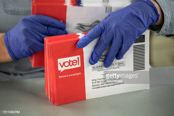 An election worker wearing protective gloves sorts through mailed-in ballots in the King County Elections ballot processing center on March 09, 2020...