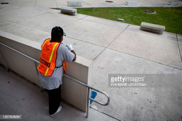 An election worker wears protective gloves during the Florida Democratic primary election outside Jose Marti Gymnasium in Miami Florida on March 17...
