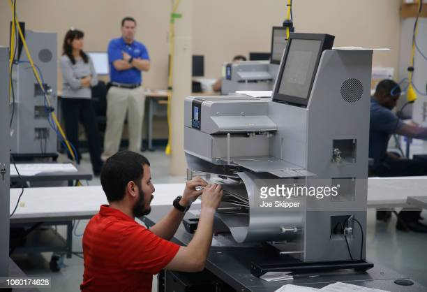 An elections official works on a counting machine as it was calibrated prior to the start of a recount of all votes at the Broward County Supervisor...