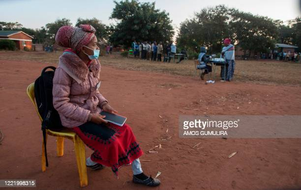 An Elections Party Monitor sits watching over queues of voters during the presidential elections at the Malembo polling station in Lilongwe on June...