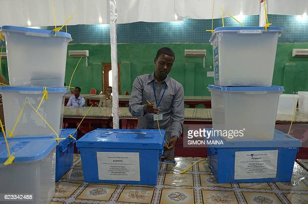 An electoral agent closes ballot boxes with cable ties as he awaits their collection in Kismayo on November 15 2016 Somalia is in the process of...