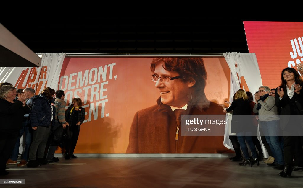 An electoral billboard with the image of 'Junts per Catalonia' (All for Catalonia) grouping cadidate for the upcoming Catalan regional election, Carles Puigdemont, is unveiled during the campaign opening meeting in Barcelona, on December 4, 2017. Catalans remain deeply split on independence, and several polls suggest pro-secession parties might struggle to win enough seats to form a new regional government after the December 21 regional election. GENE