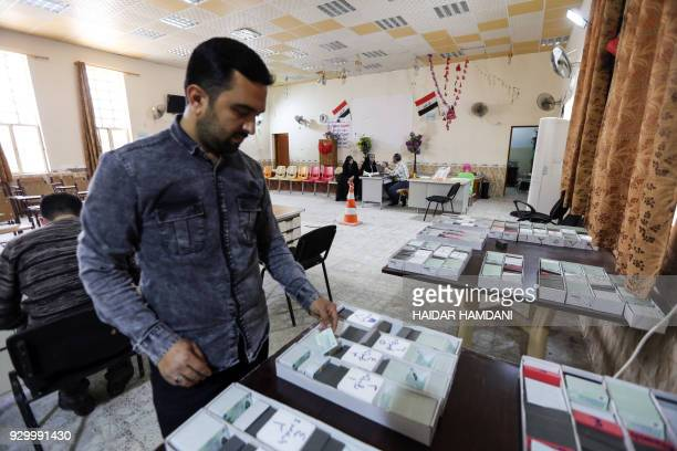An electoral commission employee sorts updated voter IDs for the upcoming May 2018 parliamentary elections at a commission office in the Holy city of...