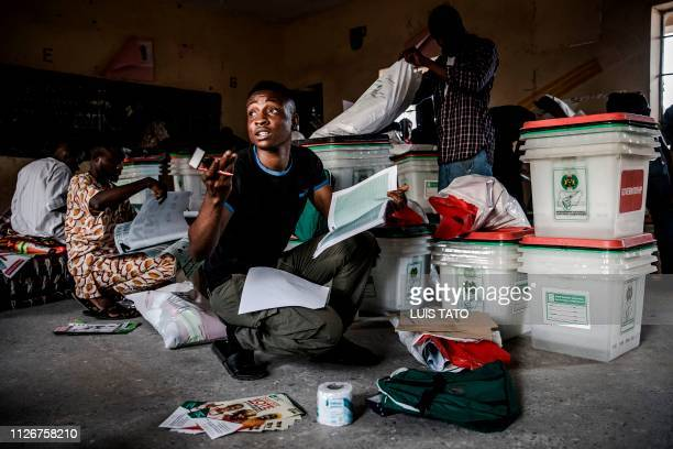 TOPSHOT An electoral commission official checks voting material at a polling station set up in the Shagari Day Secondary School in Yola in Nigeria's...