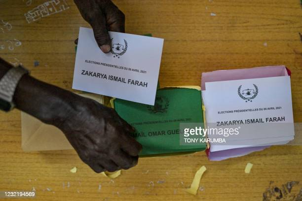 An electoral commission official collects ballot cards bearing the names of the two presidential contenders to hand them to a voter at the Ras-Dika...