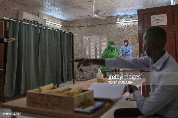 An electoral commission official gestures to an elderly woman voter , pointing her in the direction of the ballot box, at the Ras-Dika district...