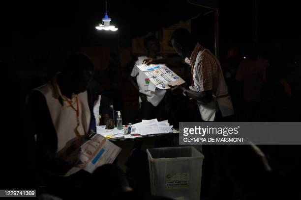 An electoral commission official holds a ballot paper during vote counting at a polling station during Burkina Faso's presidential and legislative...