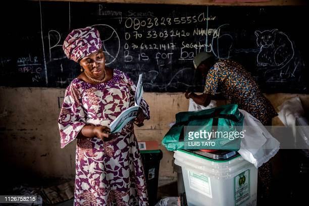An electoral commission official reads an electoral manual while some ballot boxes and other voting material are checked at a polling station set up...