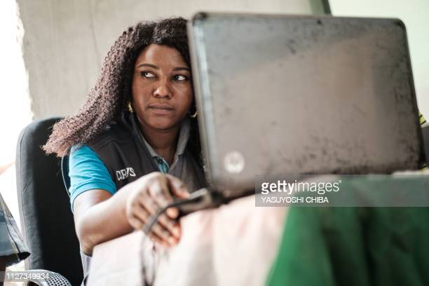 An electoral officer of the Independent National Electoral Commission looks on as she inputs numbers on a laptop as a collation officer reports the...