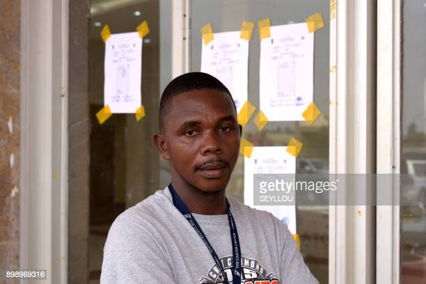 An electoral officer poses near post vote count forms on a window at Monrovia Stadium as officials count votes on December 27 2017 following the...