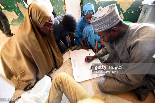 An electoral officers tries to record number of votes after the election at a polling station in Kano commercial capital of northern Nigeria on...
