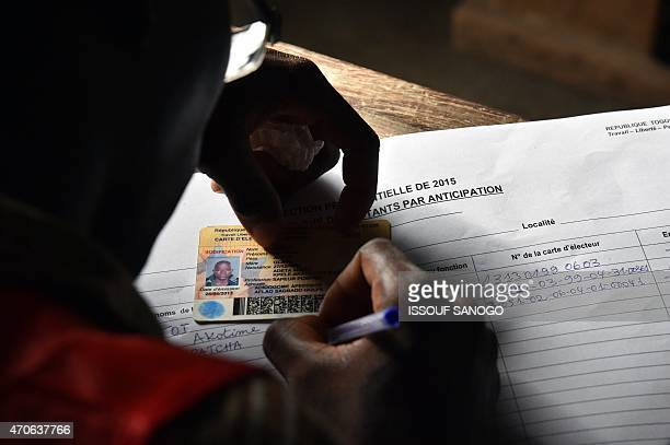 An electoral official checks an ID at a polling station in Lome on April 22 2015 as Togolose law enforcement oficers vote in the presidential...