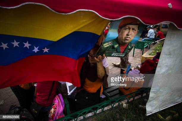 An electoral official looks past a Venezuelan flag and an image of late Venezuelan president Hugo Chavez at a checkpoint outside a polling station...
