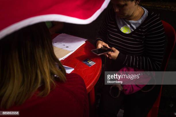 An electoral official scans a Quick Response code on a government issued 'Carnet de La Patria' electronic identity card at a checkpoint outside a...