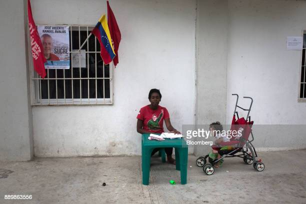 An electoral official wearing a tshirt displaying the image of late Venezuelan president Hugo Chavez sits at a checkpoint outside a polling station...
