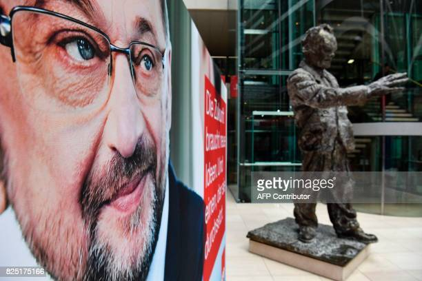 An electoral poster featuring SPD chairman and candidate for chancellery Martin Schulz is displayed next to the statue of late former SPD chancellor...