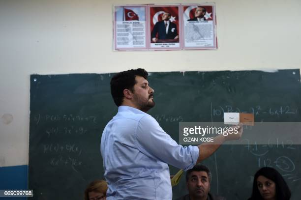 An electoral staff member shows a 'No' vote as ballots are counted after the polls closed during the referendum on expanding the powers of the...