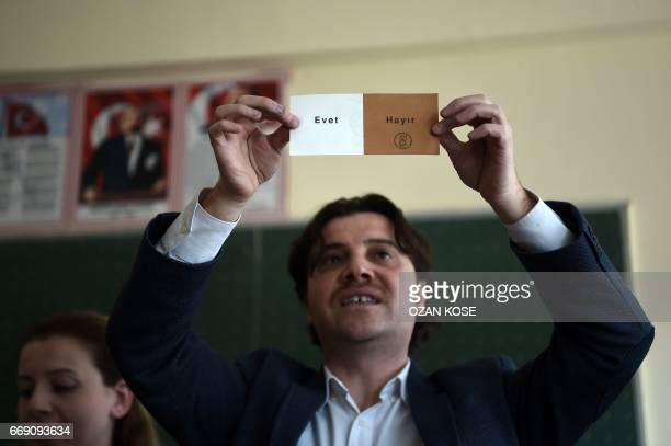 An electoral staff member shows a 'No' vote as they count ballots after the polls closed during the referendum on expanding the powers of the...