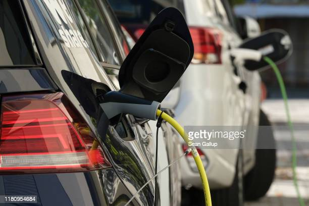 An electric car and a plug-in hybrid car charge at a public charging station on October 12, 2019 in Berlin, Germany. Germany is hoping to encourage...
