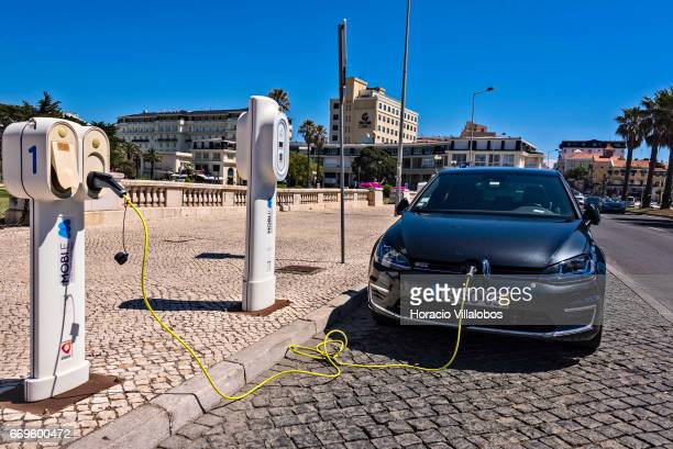 An electric car charges its batteries at a 'MOBIE' charging post in front of the train station on April 16 2017 in Estoril Portugal Portugal has...