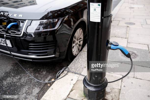 An electric car is connected to a public charging station in London England on August 15 2020 London encourages more electric cars in the city by...