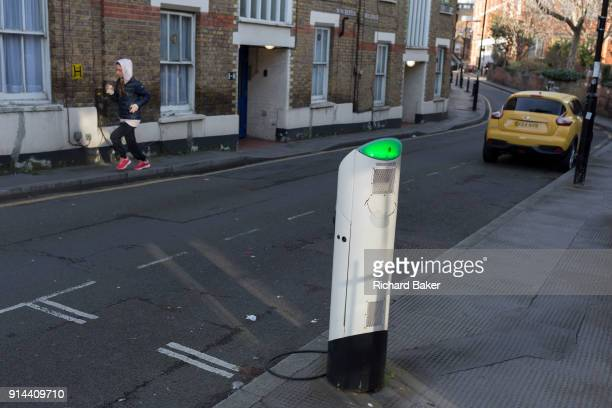 An electric car recharging point and a jogger on 30th January 2018 in the south London borough of Southwark England