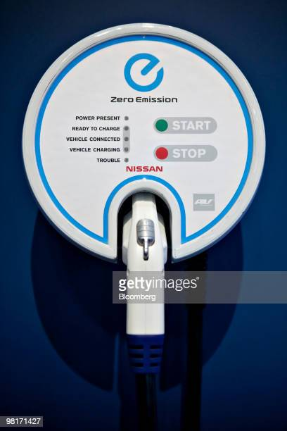 An electric charging station hangs near a Nissan Leaf electric vehicle on display during a media preview of the New York International Auto Show in...