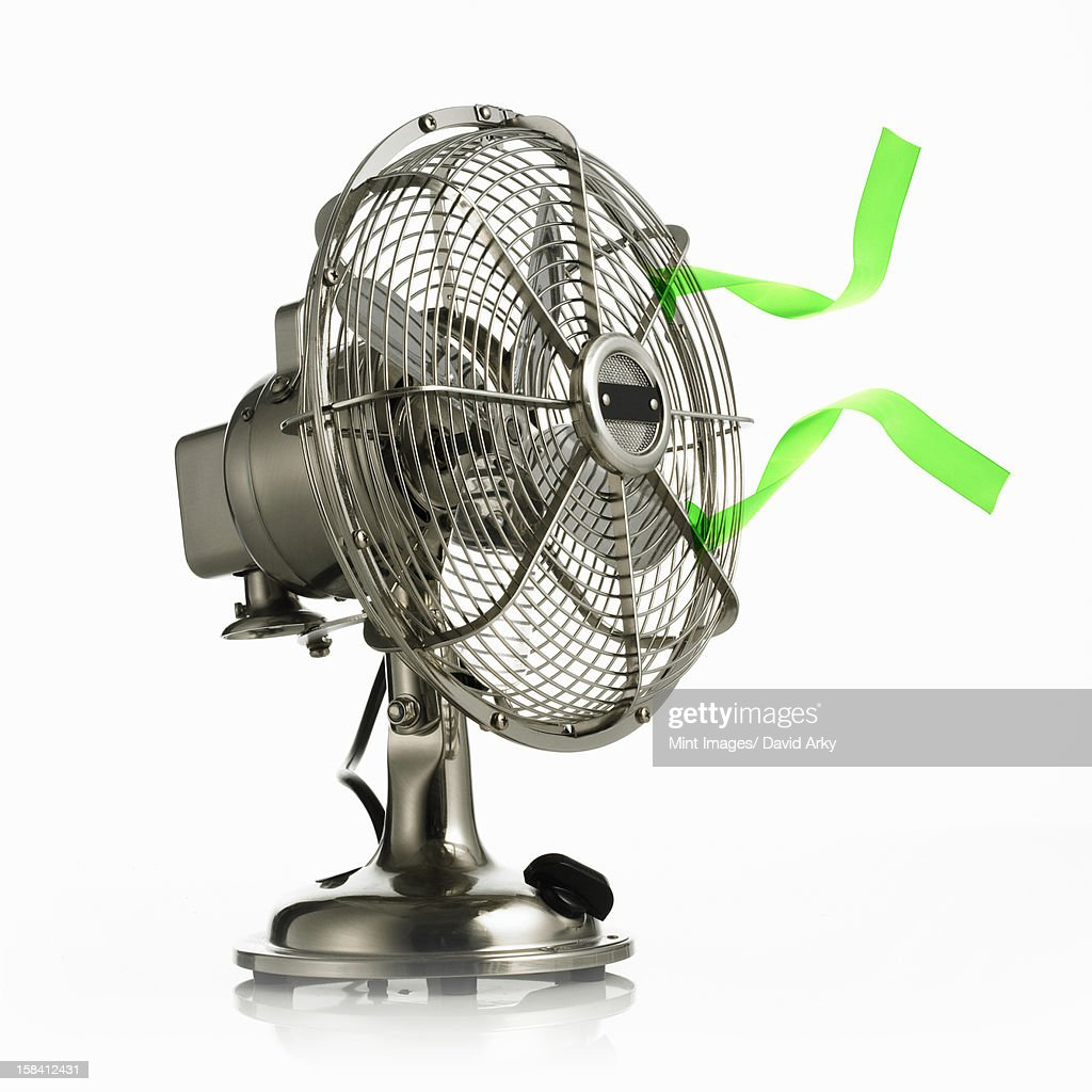 An electric fan with protective cage around the moving parts, and green streamers waving in the breeze. : Stock Photo