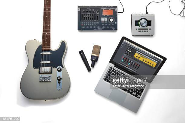 An electric guitar Apple MacBook and a selection of audio hardware photographed for a feature on recording music including a Universal Audio Apollo...