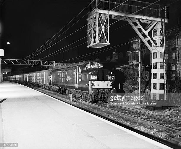An electric locomotive 14M17 pulling a train carrying Ford cars from Dagenham to Barking at night Industries were now relying more and more heavily...