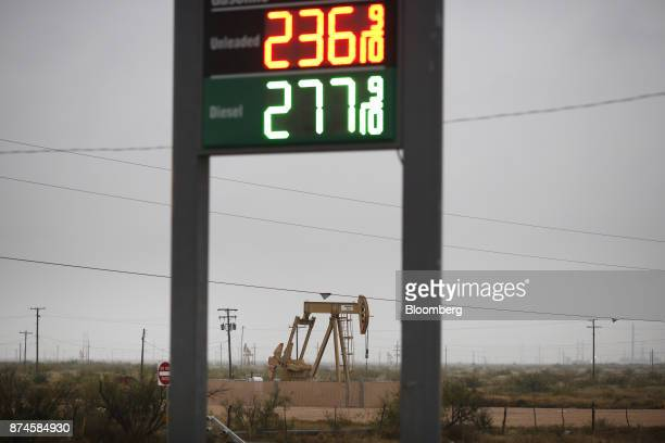 An electric oil pump jack stands past a sign displaying fuel prices at a gas station in Midland Texas US on Wednesday Nov 8 2017 Nationwide gross oil...