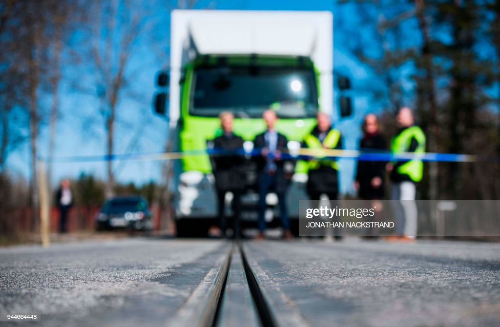 An electric rail, part of the first 'eRoad' of its kind, an approximately two-kilometer-long electrified road, is pictured in front of a truck, on April 11, 2018 at Arlanda airport, north of Stockholm. This eRoadArlanda is an example of a sustainable and cost-effective solution to enable the electrification of existing commercial roads. The electrified road, a Swedish innovation, is the first of its kind in the world and allows both commercial and passenger vehicles to be recharged while driving. PHOTO / Jonathan NACKSTRAND