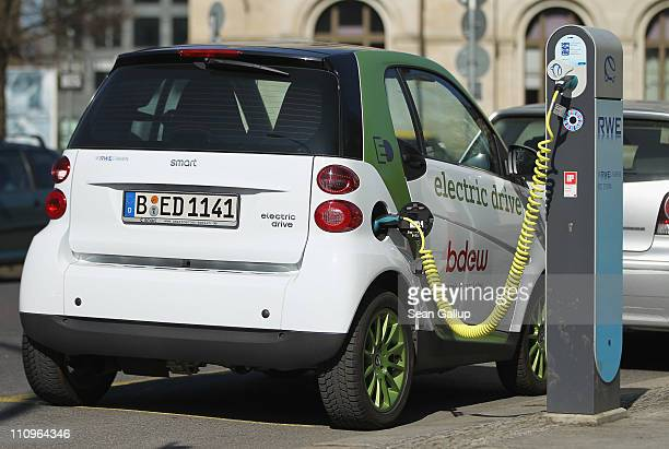 An electric Smart car charges at a public charging station on March 28 2011 in Berlin Germany The city of Berlin has teamed up with several auto...