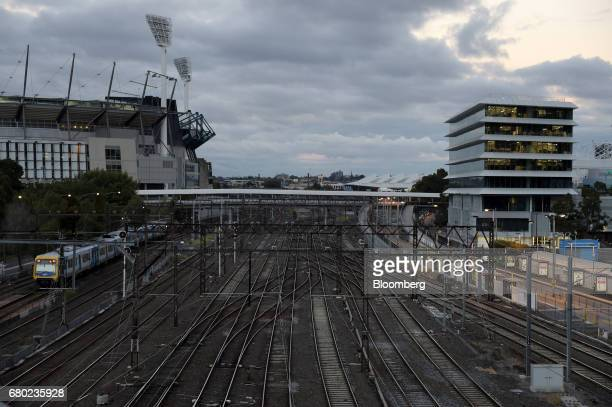 An electric train travels along a track past the Melbourne Cricket Ground left towards Flinders Street Station in Melbourne Australia on Friday April...