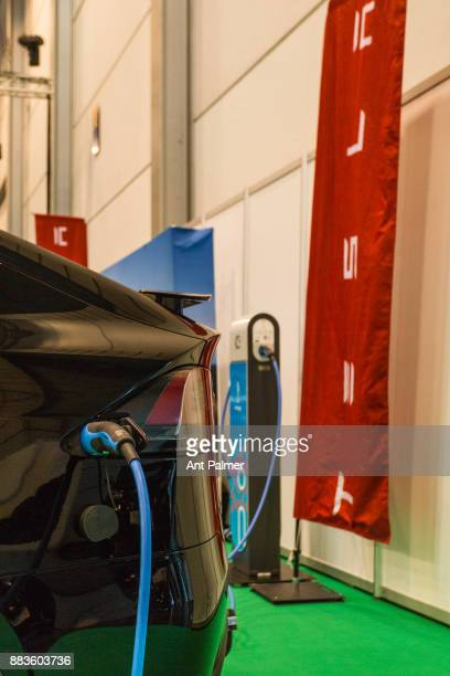 An electric vehicle from US manufacturer Tesla is connected to a charging station at the Essen Motor Show on December 1 2017 in Essen Germany The...