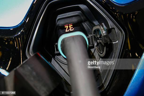 An electrical charging cable sits connected to a demonstration model of a new battery-powered Zoe city car, manufactured by Renault SA, during the...