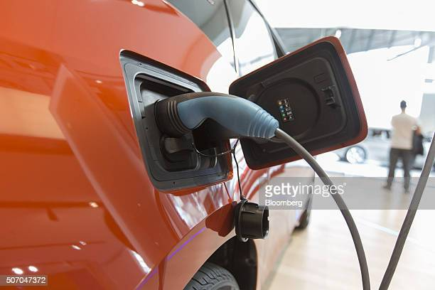 An electrical plug sits connected to a BMW i3 plugin automobile produced by Bayerische Motoren Werke AG inside the BMW World showroom in Munich...
