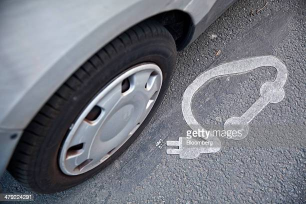 An electrical plug symbol sits on a road surface beside a Autolib' electric automobile manufactured by Groupe Bollore at a public carsharing scheme...