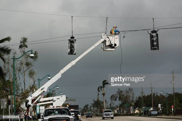 An electrical worker repairs stop lights the morning after Hurricane Irma swept through the area on September 11 2017 in Naples Florida Hurricane...